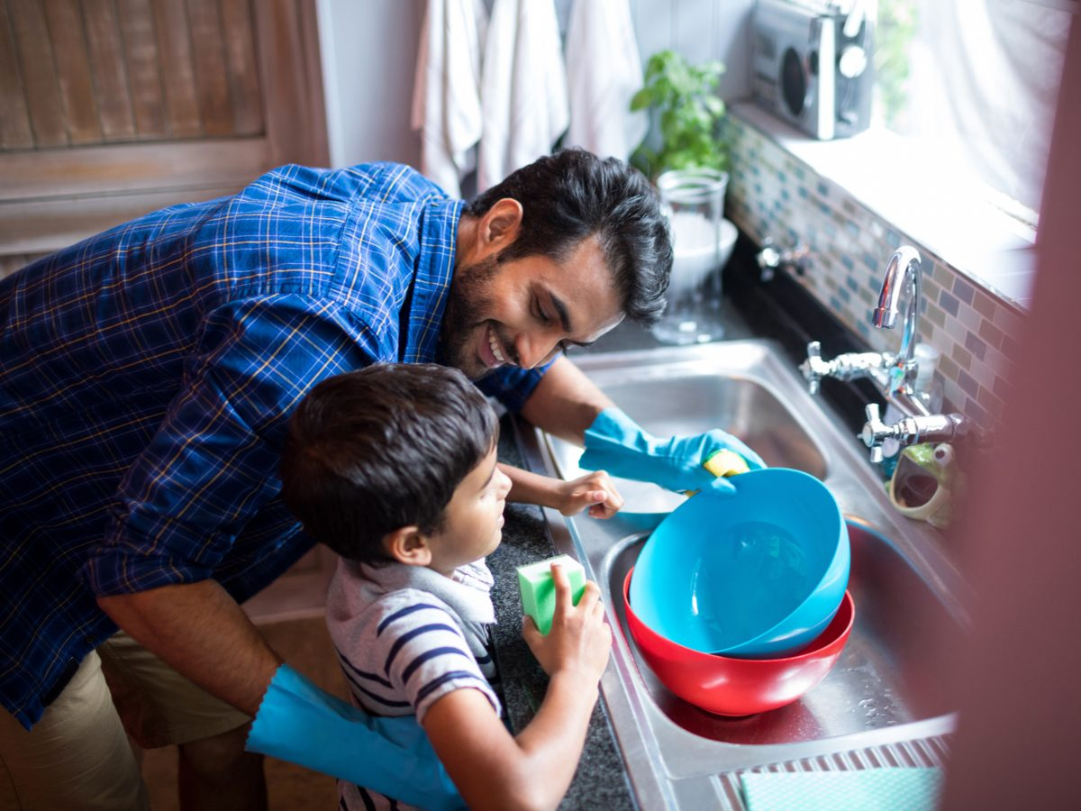 Father and son cleaning dishes in the kitchen