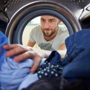 laundry tips - man reaching into dryer