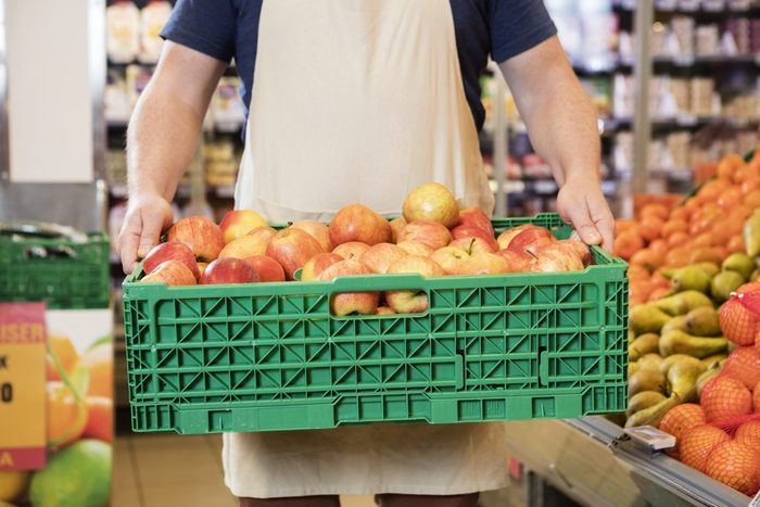 Produce section - Worker carrying crate of apples