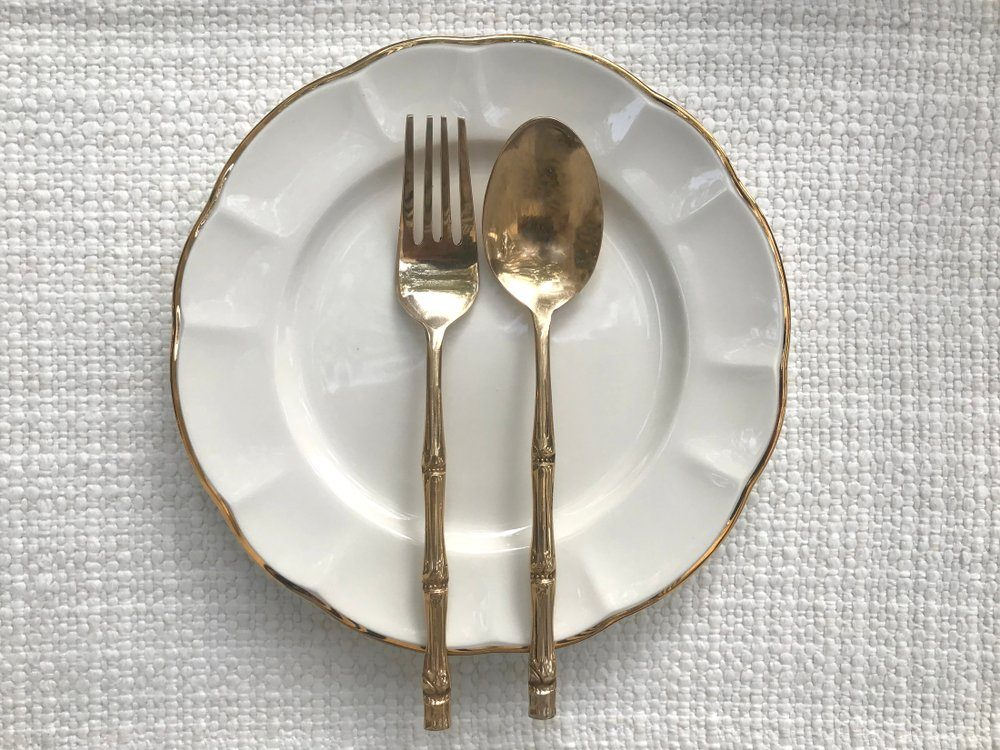 Empty white plate, fork and spoon on table