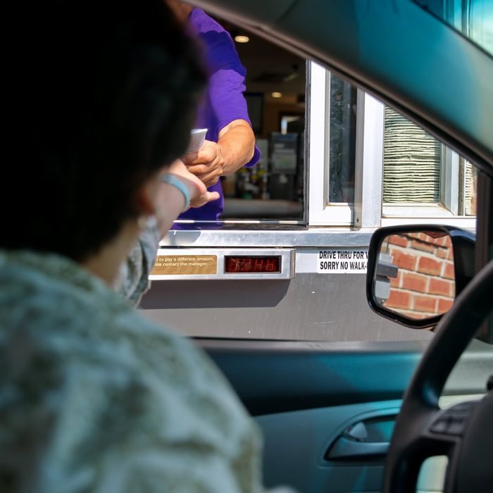 Fast food employee and customer hands in a transaction at the drive thru