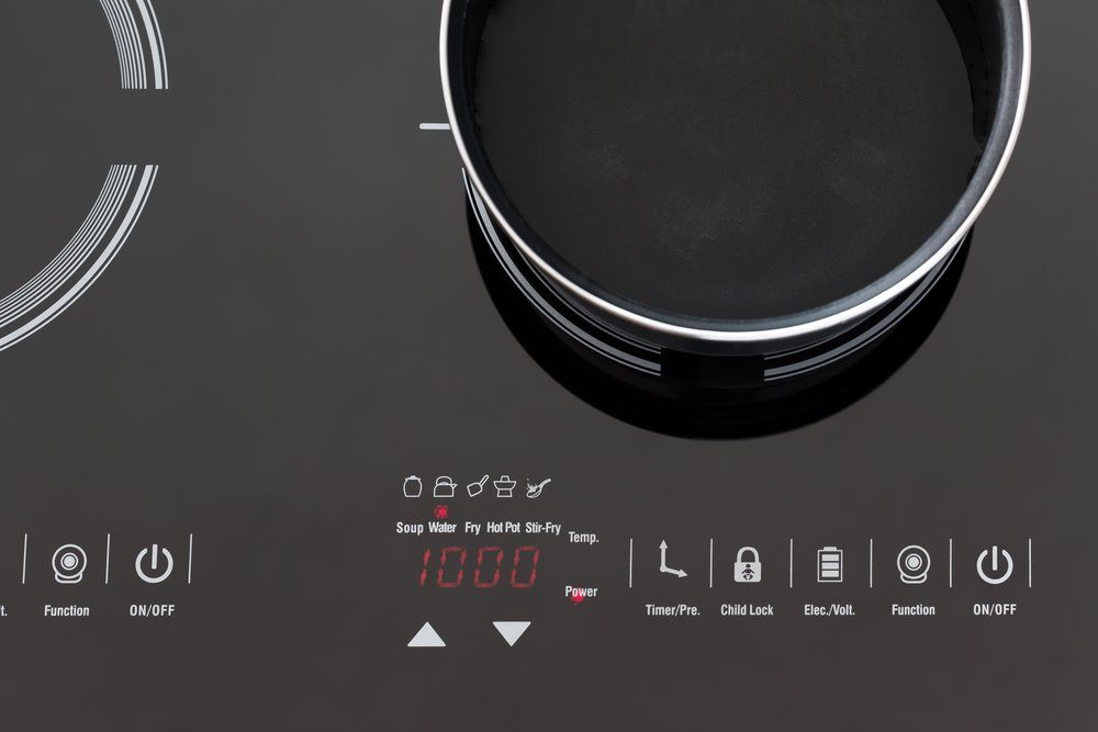 Boiling water at pan on Induction stove top panel, closeup
