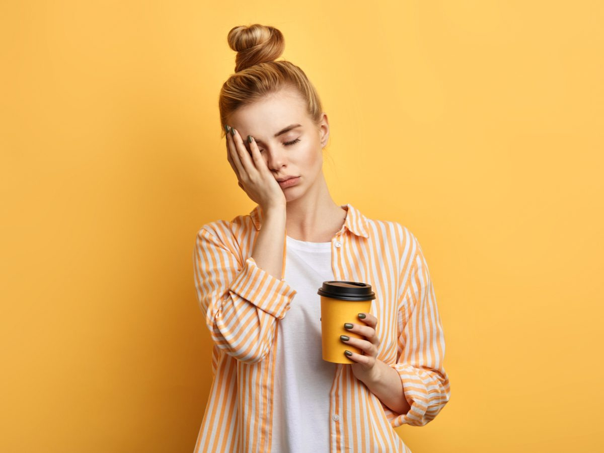 Tired sleepy woman holds a cup of coffee