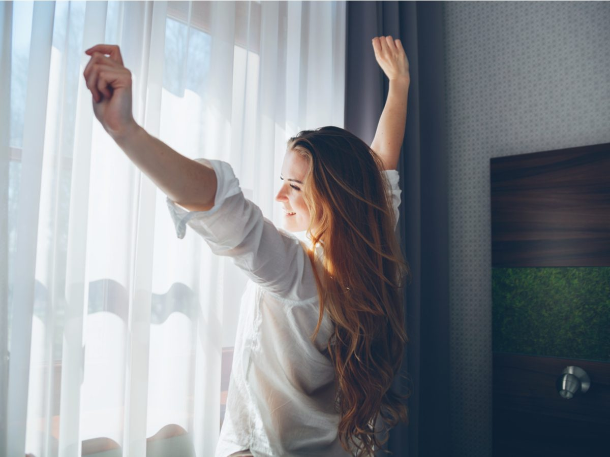 Young woman in modern apartment stretching after wake up