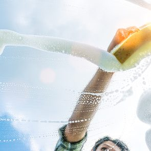 spring cleaning tips - window cleaner cleaning window with squeegee and wiper on a sunny day