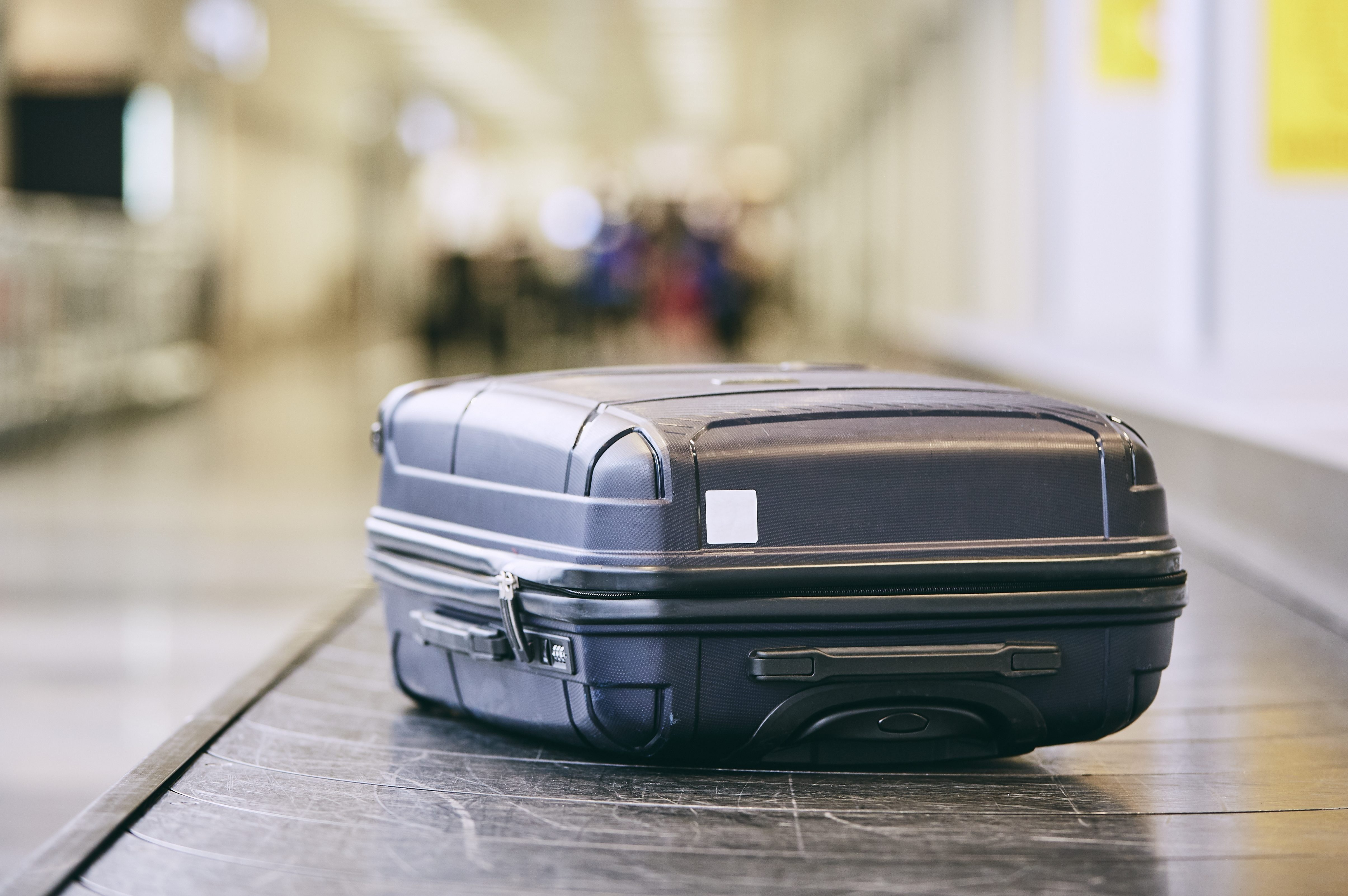 Close-Up Of Black Suitcase On Conveyor Belt At Airport