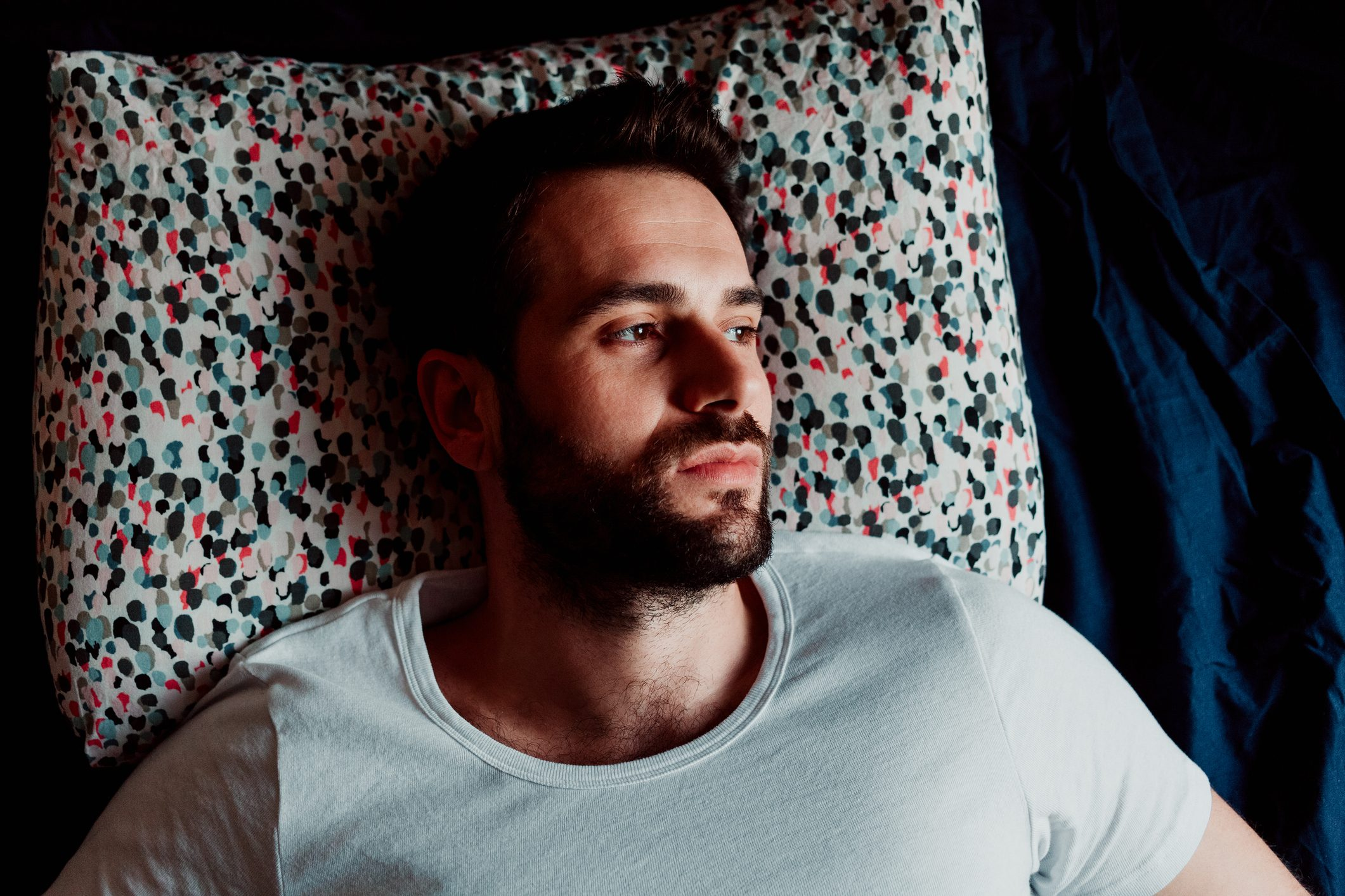 man lying in bed not able to sleep
