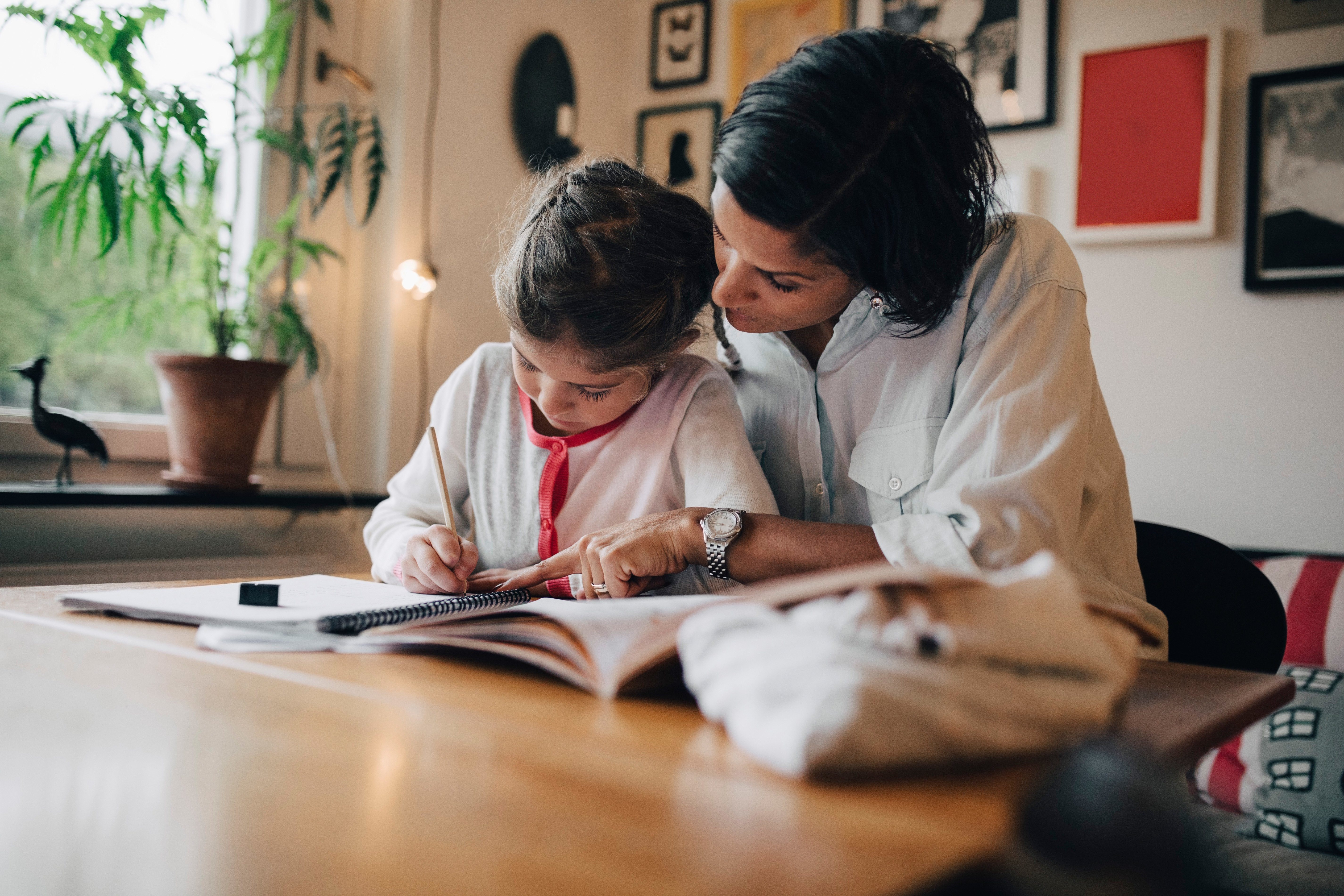 Mother assisting daughter in writing homework on table while sitting against wall at home