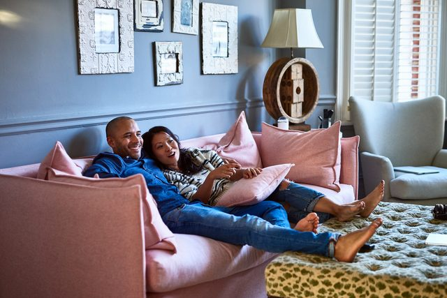 couple sitting on couch at home relaxing and laughing together