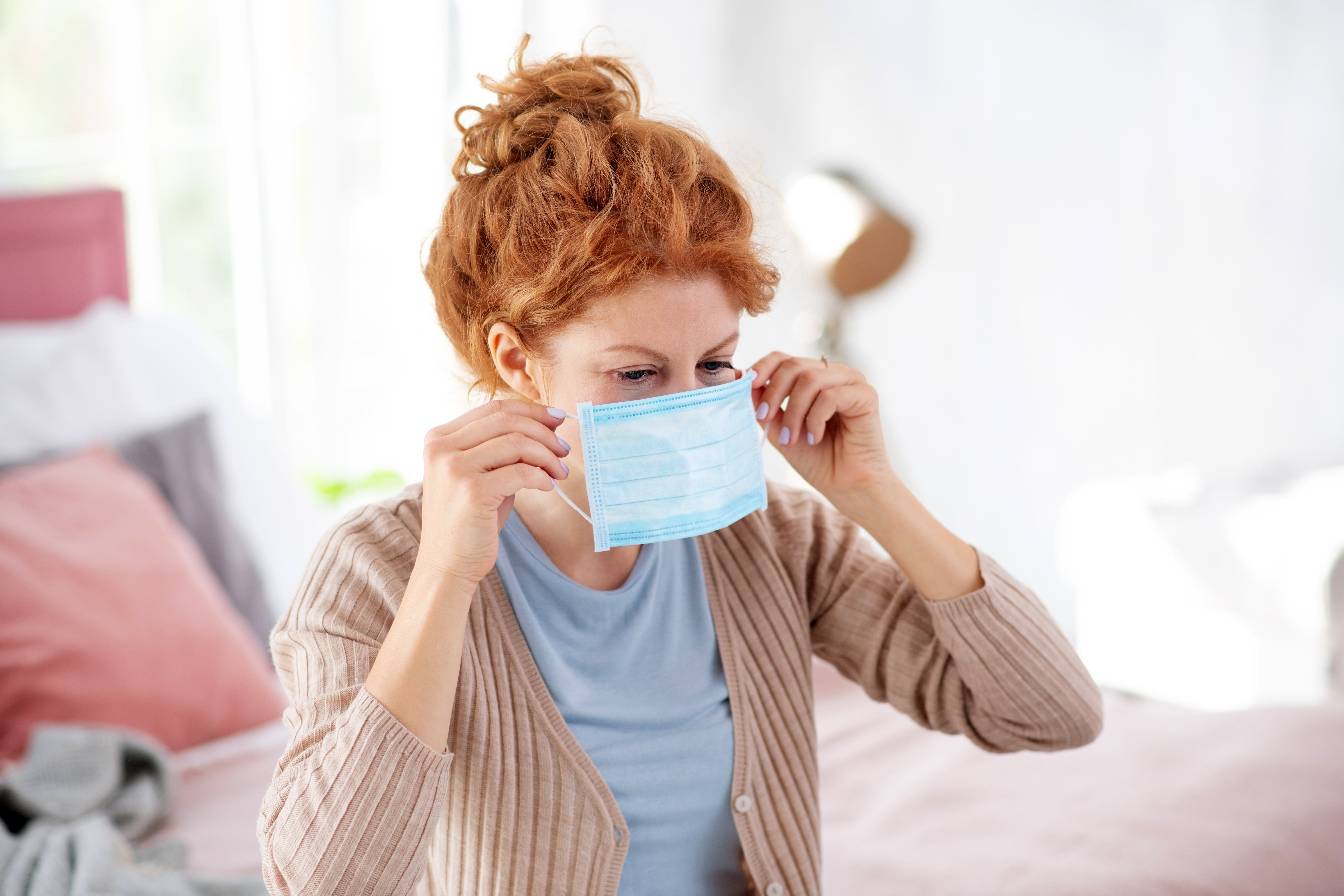 Red-haired woman putting mask on while having flu