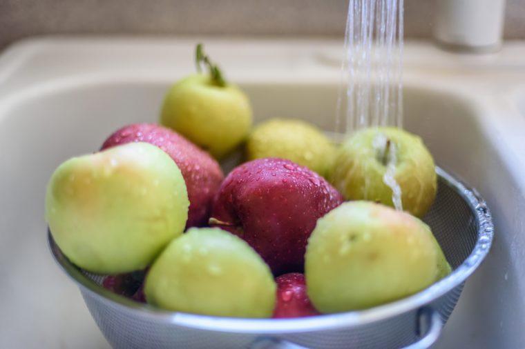 Rinsing fresh apples in the sink