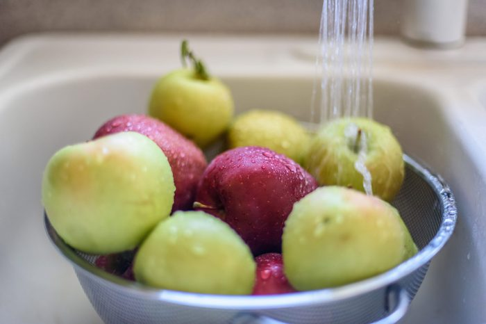 Rinsing fresh apples in the sink