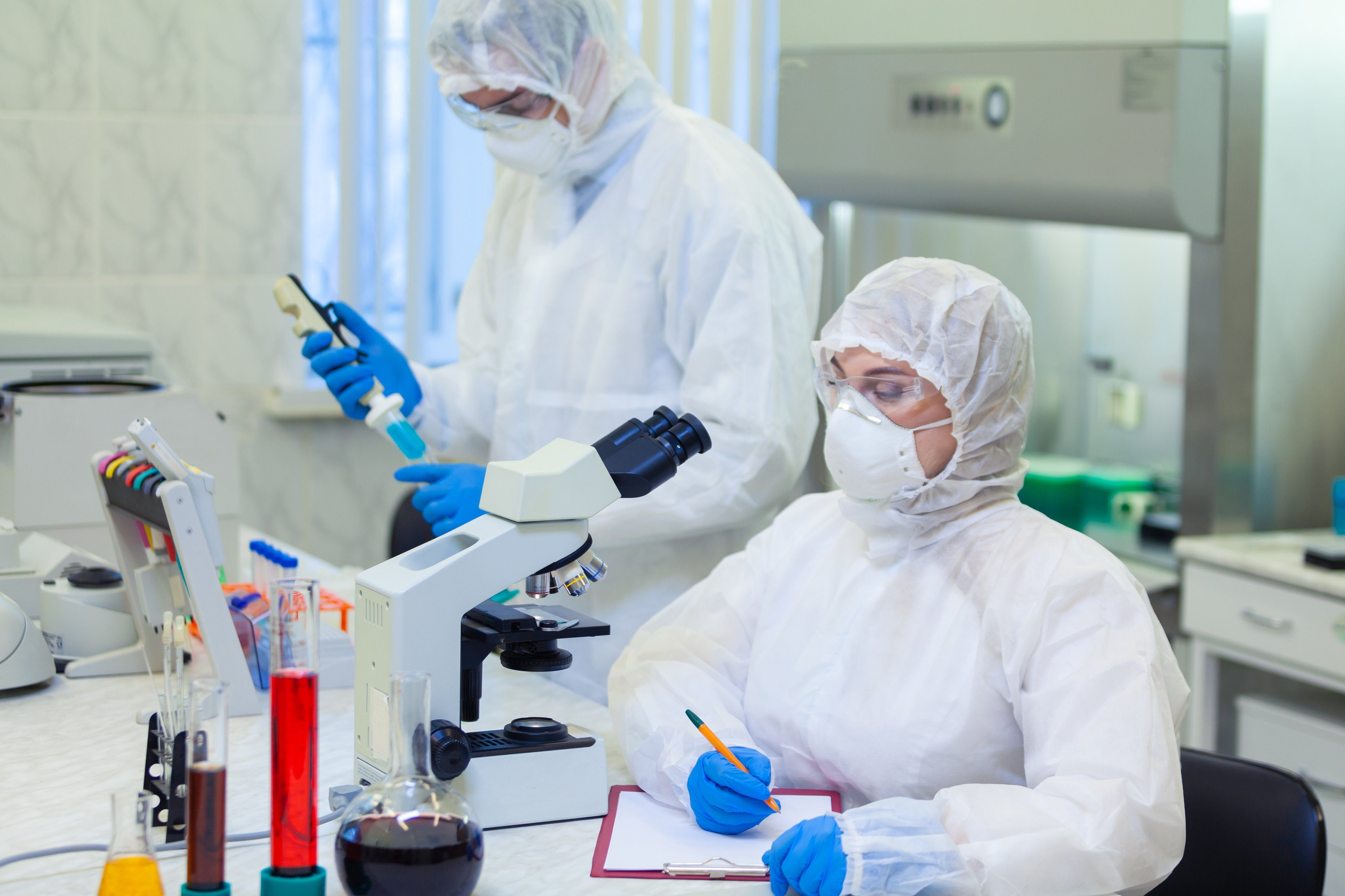 Scientists in protective suits in a science laboratory study a dangerous virus to eliminate the epidemic