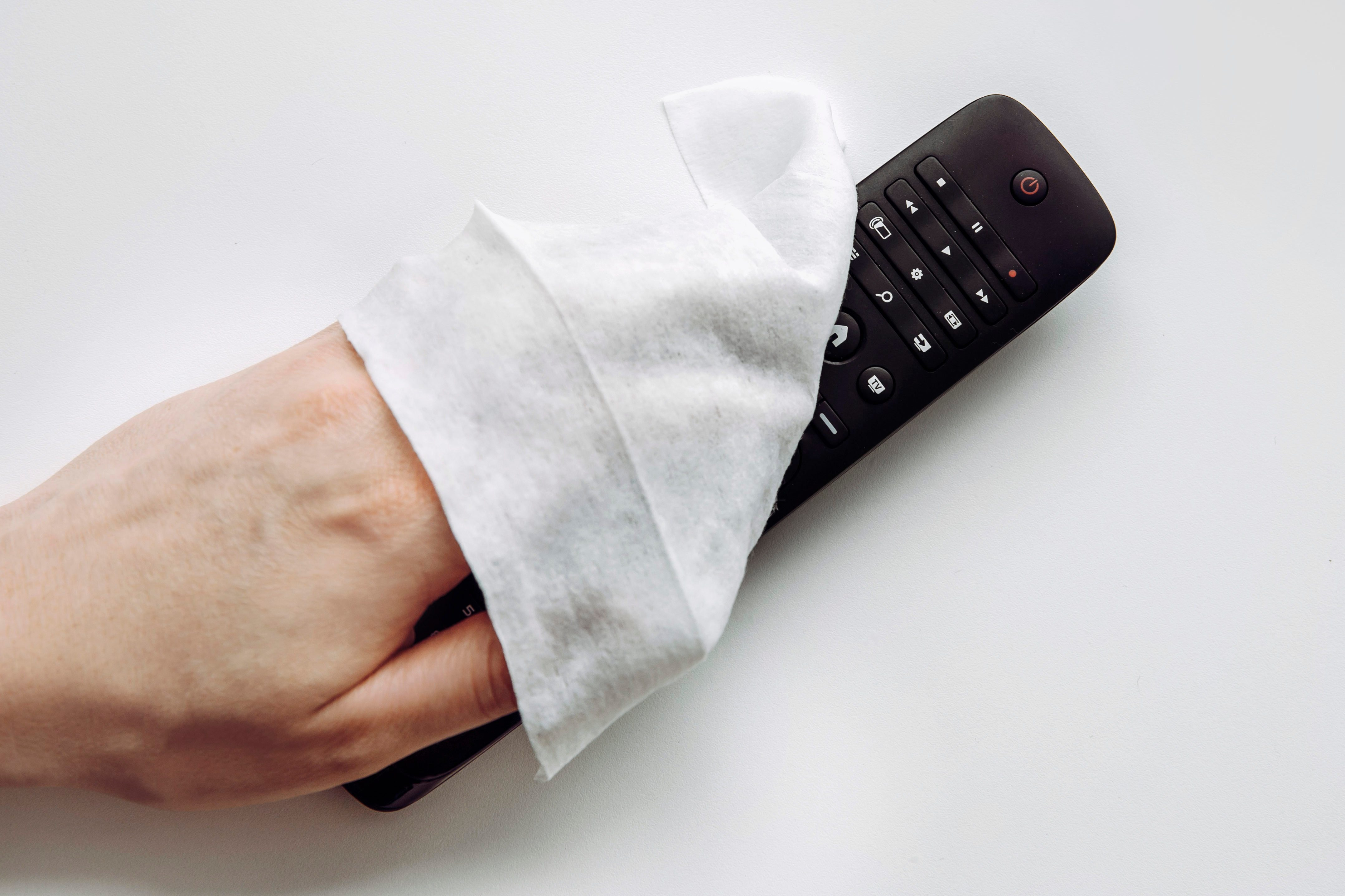 Close up view of man hand using antibacterial wet wipe for disinfecting home TV remote control.