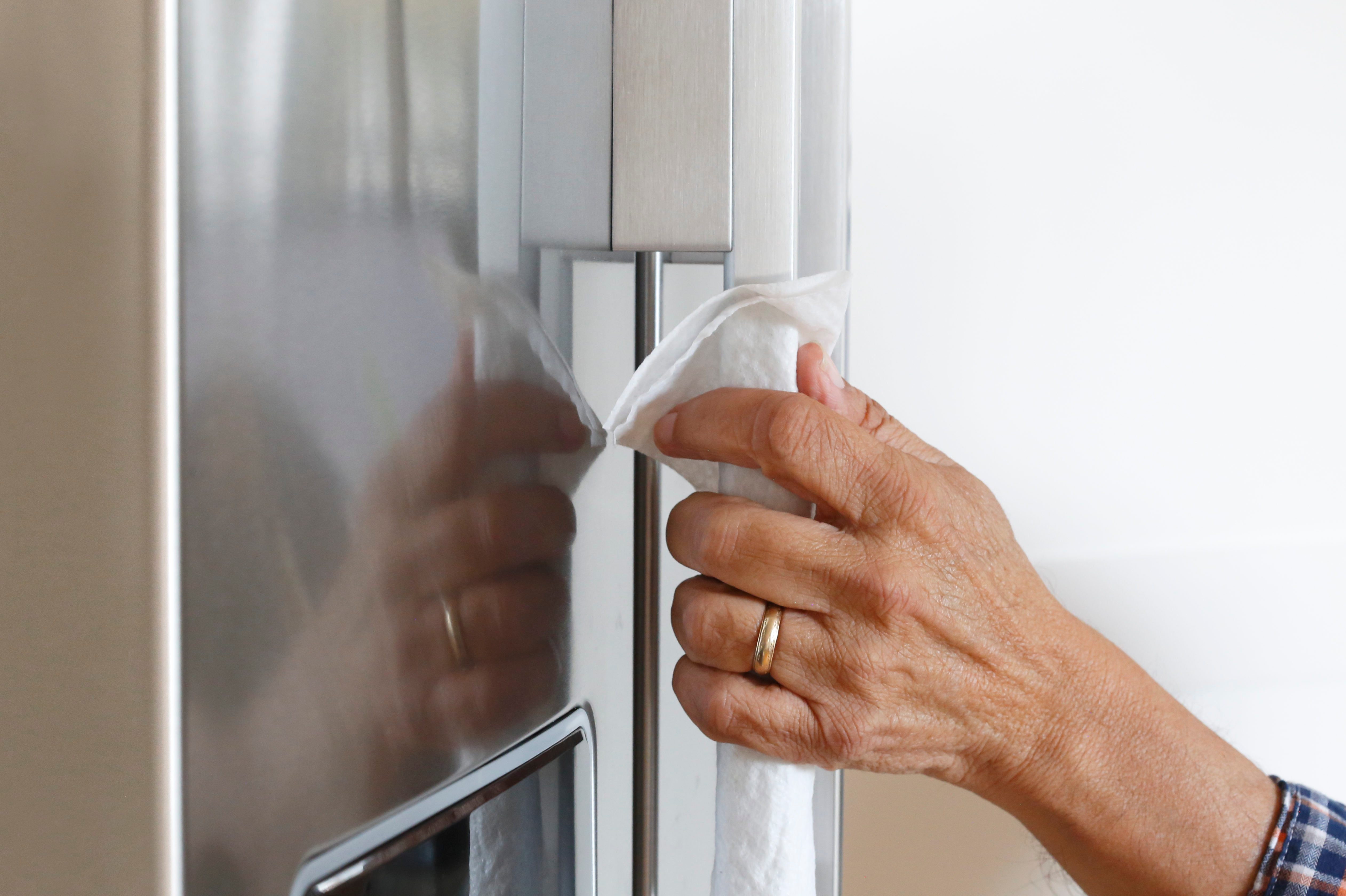 Close Up Of Man Cleaning Refrigerator With Disinfectant Wipe