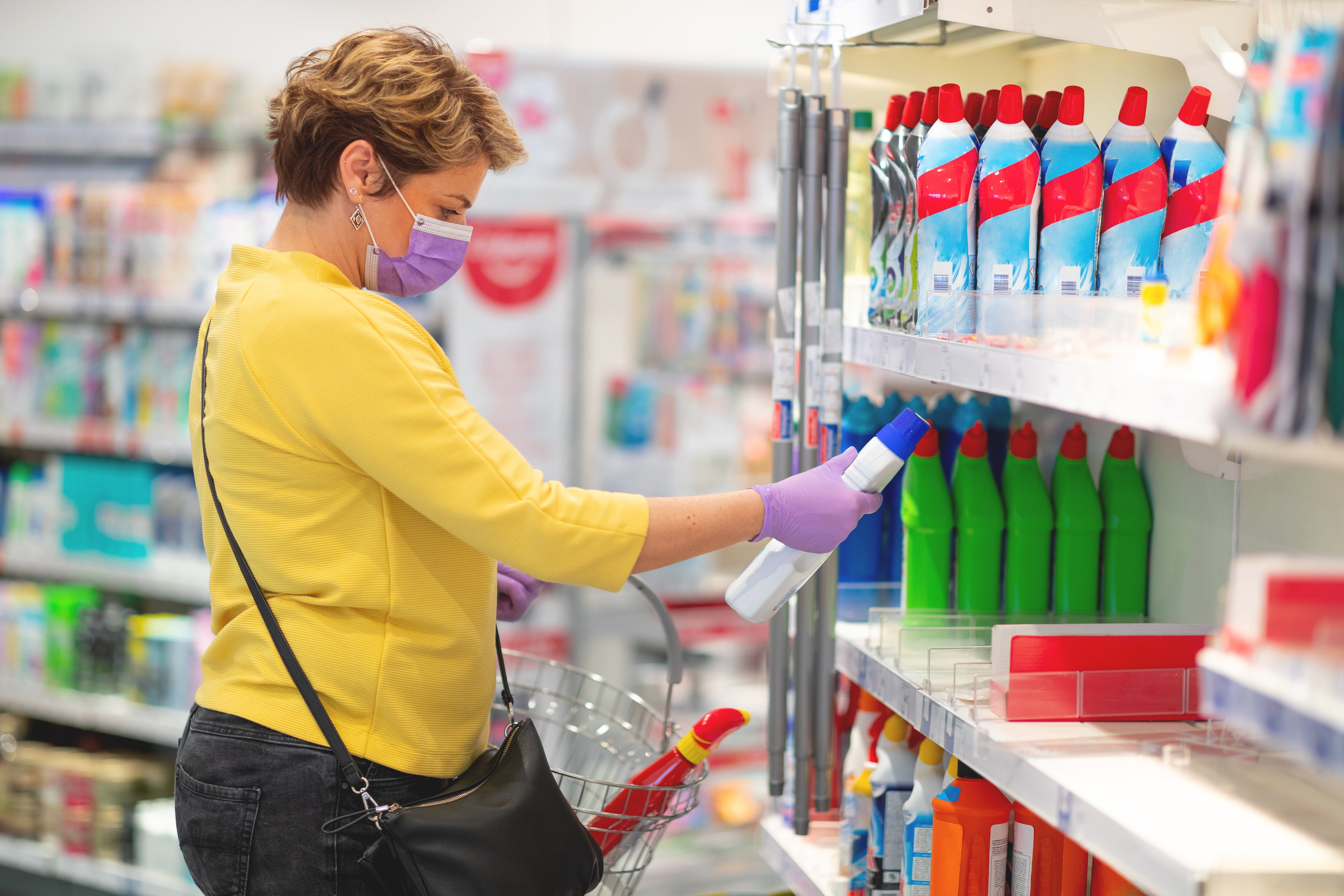 Adult woman reading label of disinfectant
