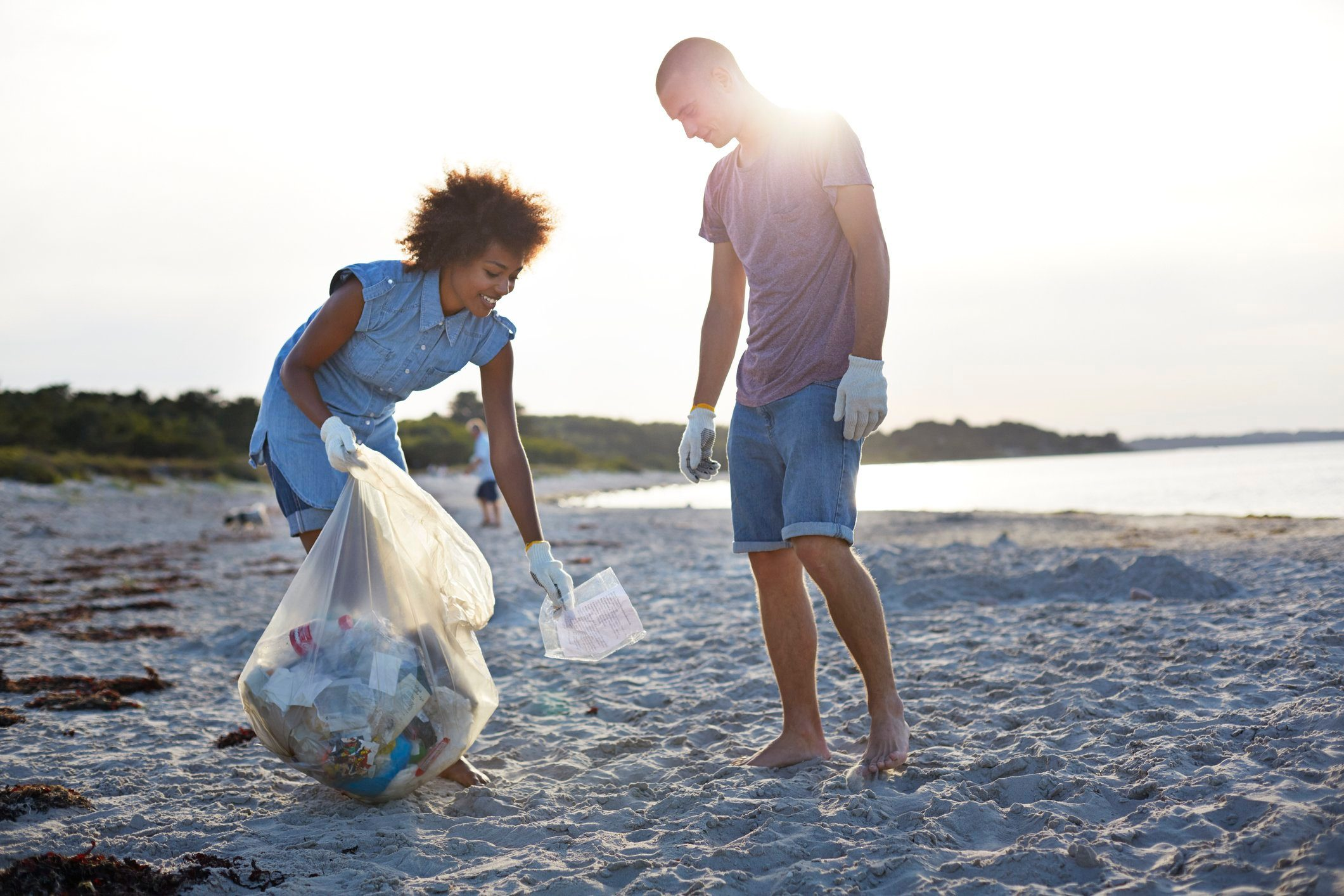 two people picking up litter on beach