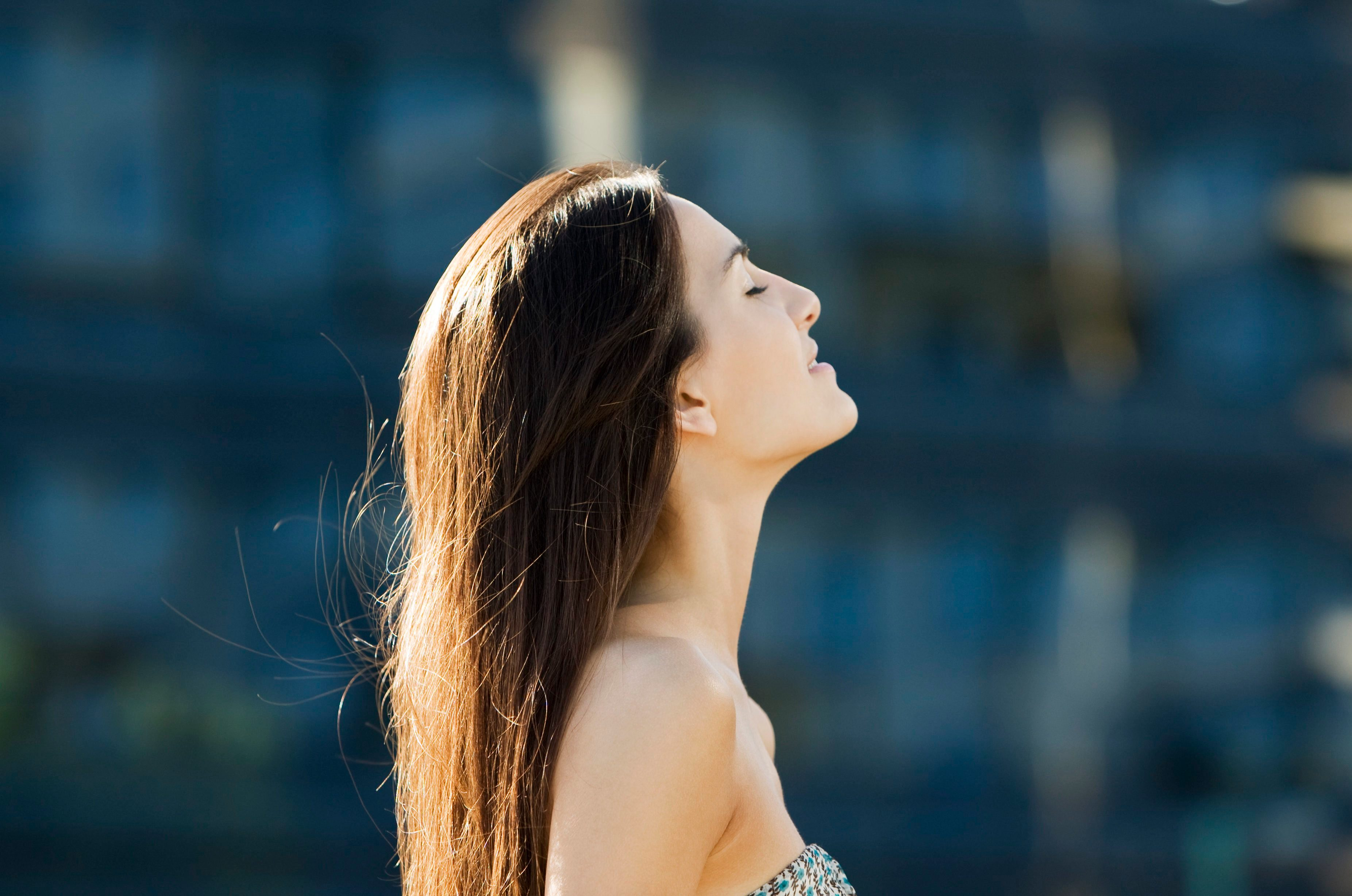 Young woman outdoors on sunny day, head back, eyes closed