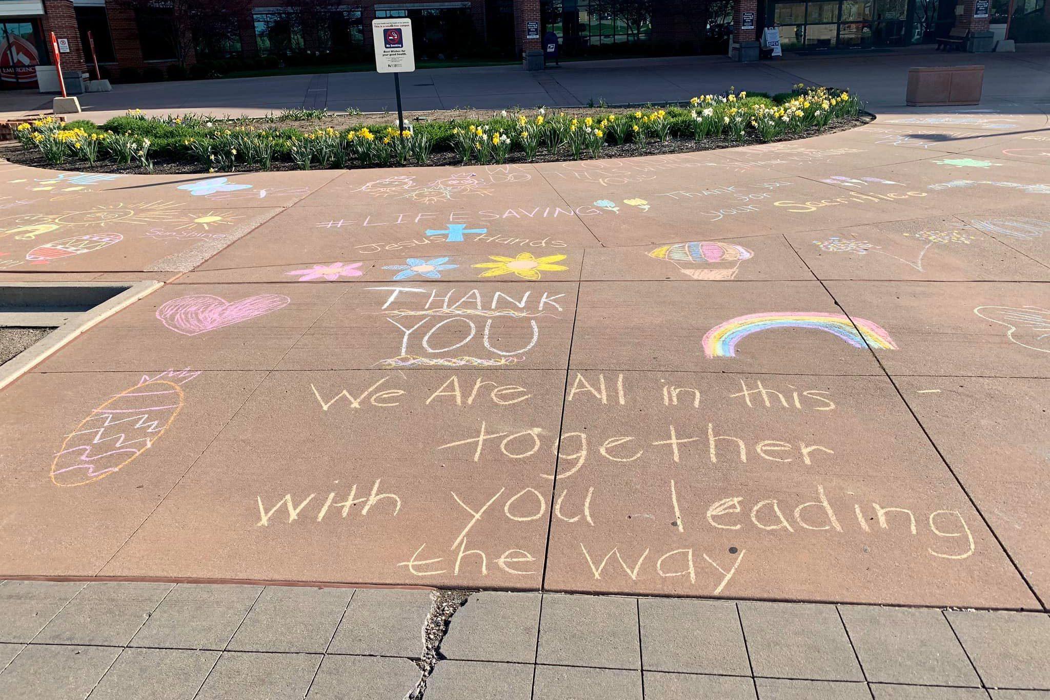 Message of kindness drawn on sidewalk in chalk