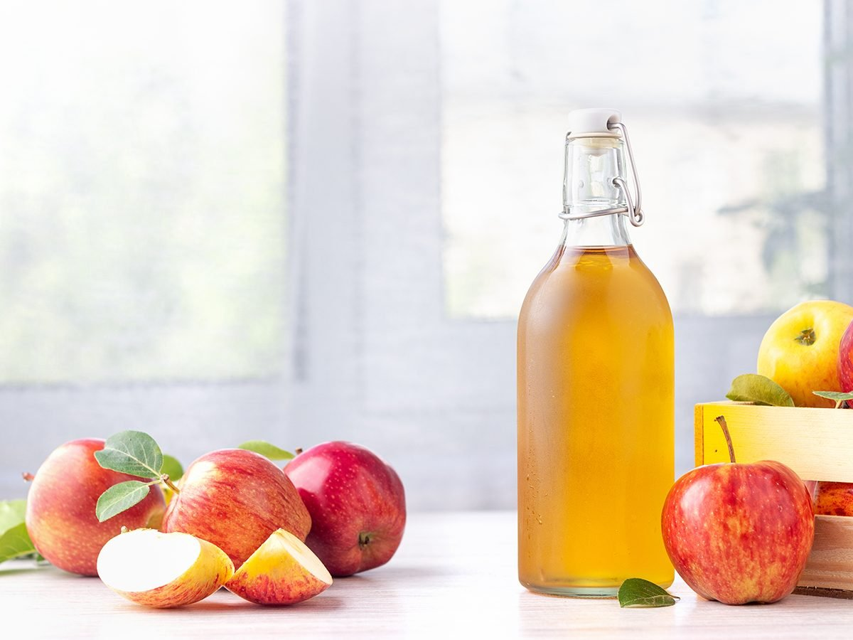 Healthy organic food. Apple cider vinegar in glass bottle and fresh red apples on a light background