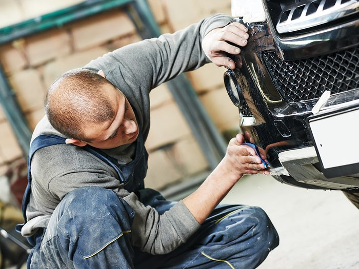 Car bumpers - auto mechanic worker sanding polishing bumper car at automobile repair and renew service station shop by sandpaper