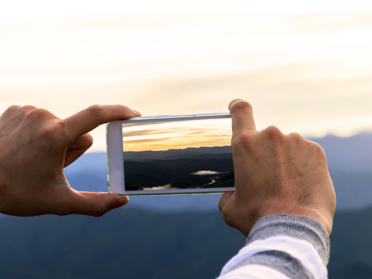 man taking sunset picture with smartphone.