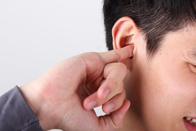 signs of hearing loss - man use finger to scratching ear