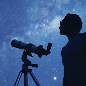 Things to do in quarantine - Man with telescope stargazing outside.