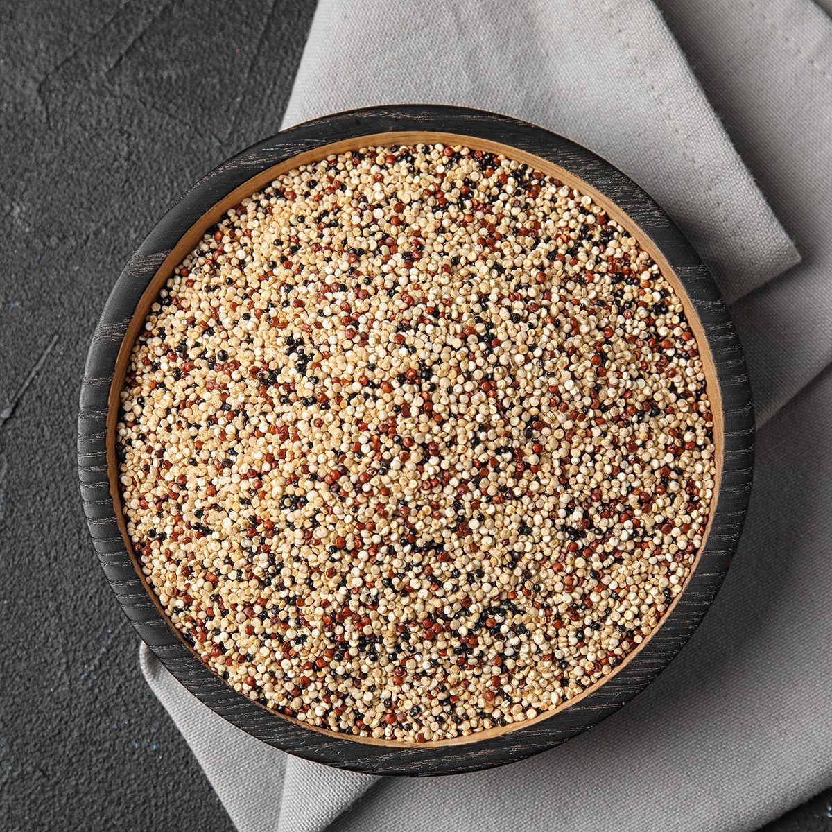 Plate with mixed quinoa seeds on dark background