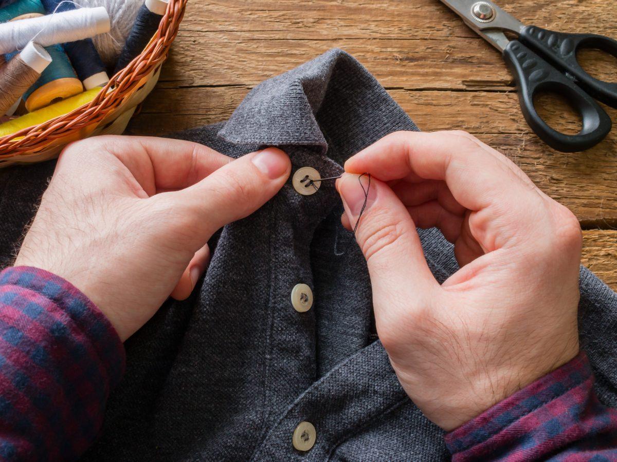 Man sewing a button onto his collar shirt