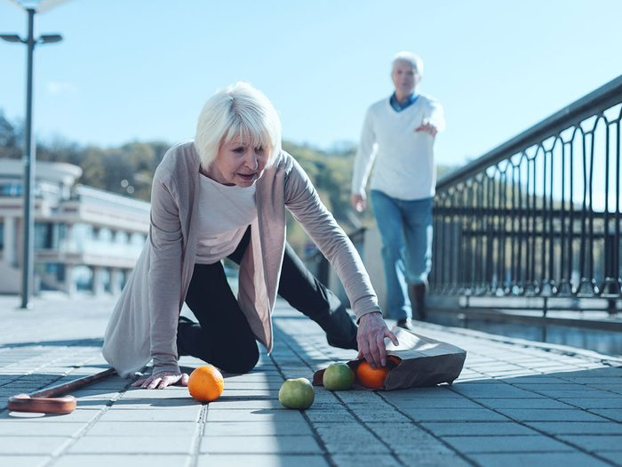 Signs of hearing loss - senior lady standing on her knee and trying to pick up her groceries after falling down while her worried husband running to her in the background