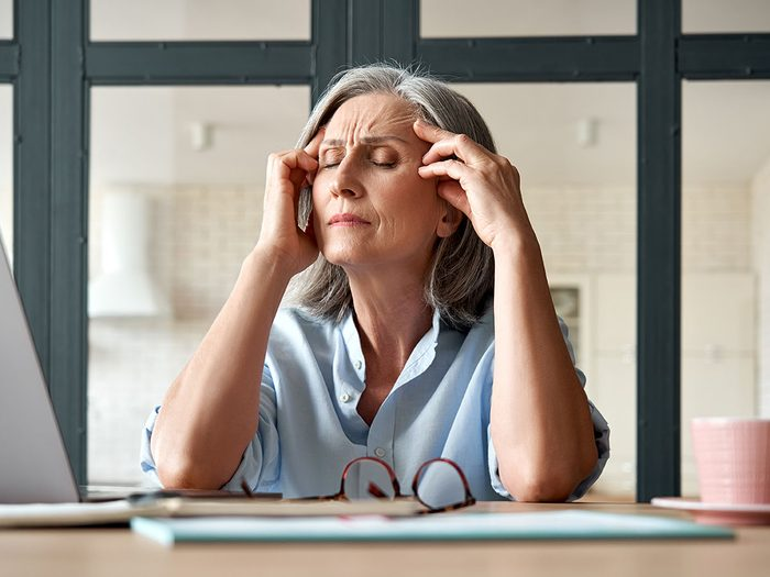 Tired stressed old mature business woman suffering from headache at work. Upset sick senior middle aged lady massaging head feeling migraine from overwork or menopause using computer at home office