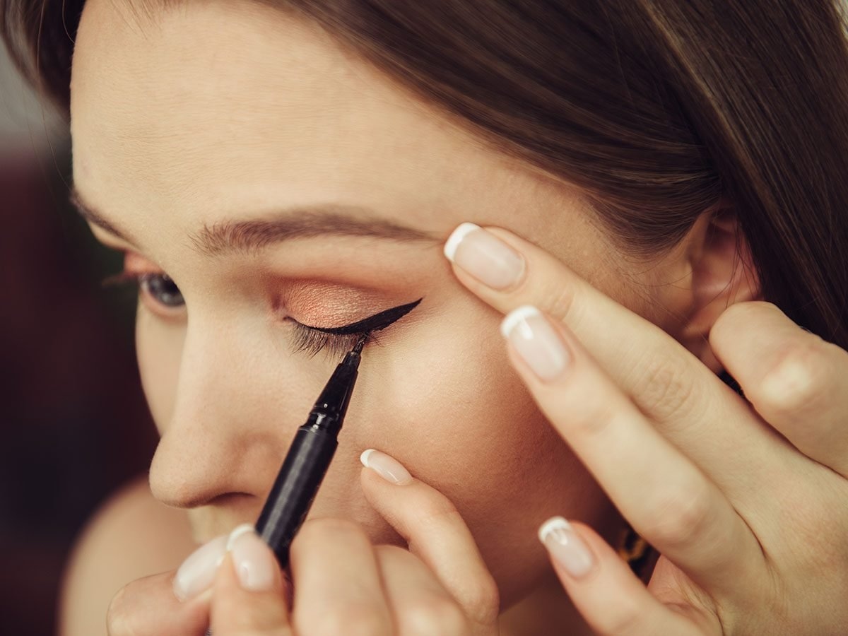 women putting on eyeliner.