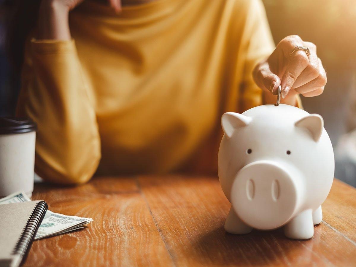 women saves money in piggy bank.
