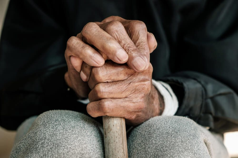older man's hands holding on to a walking stick