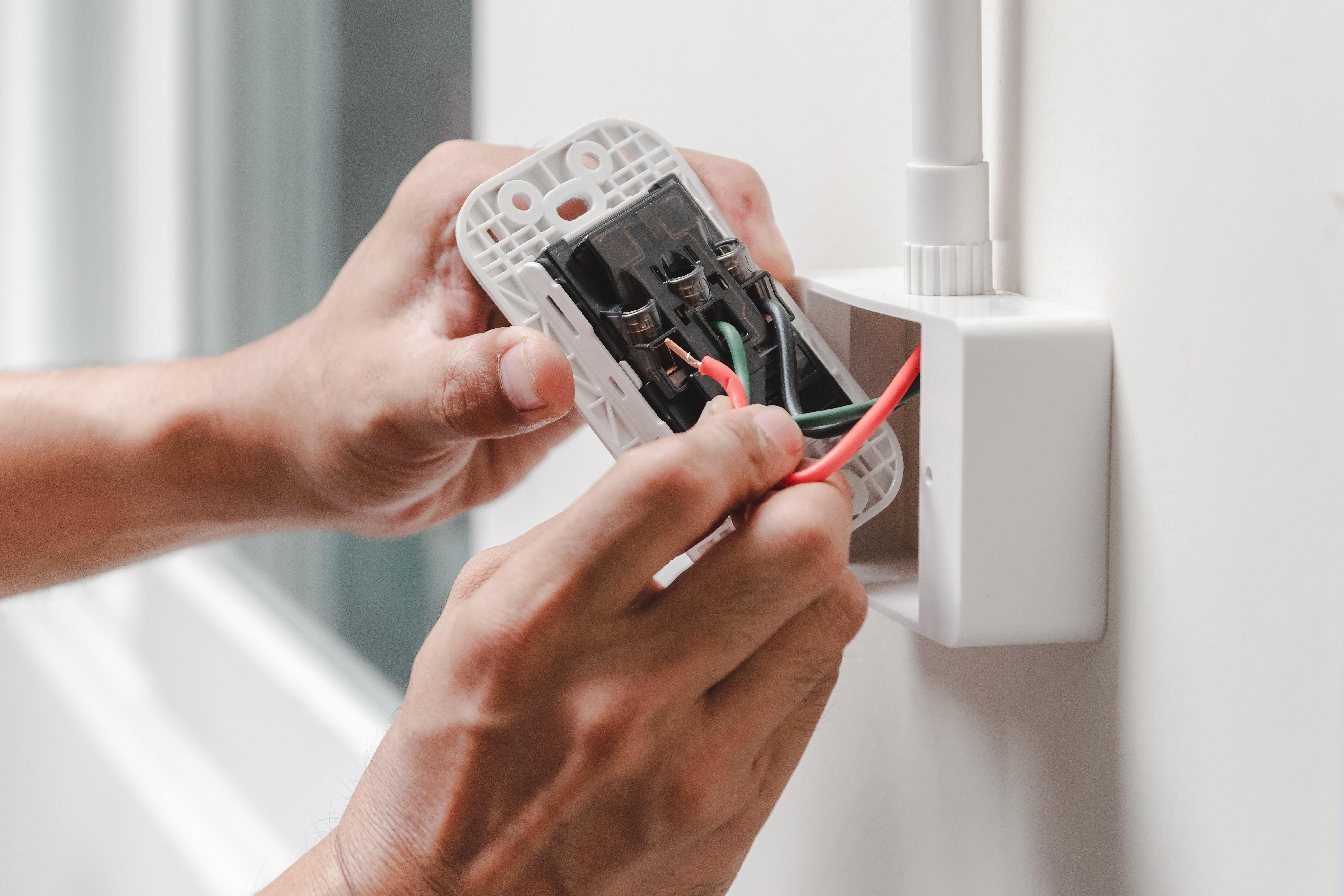 Cropped Hands Of Male Electrician Repairing Electrical Outlet On Wall