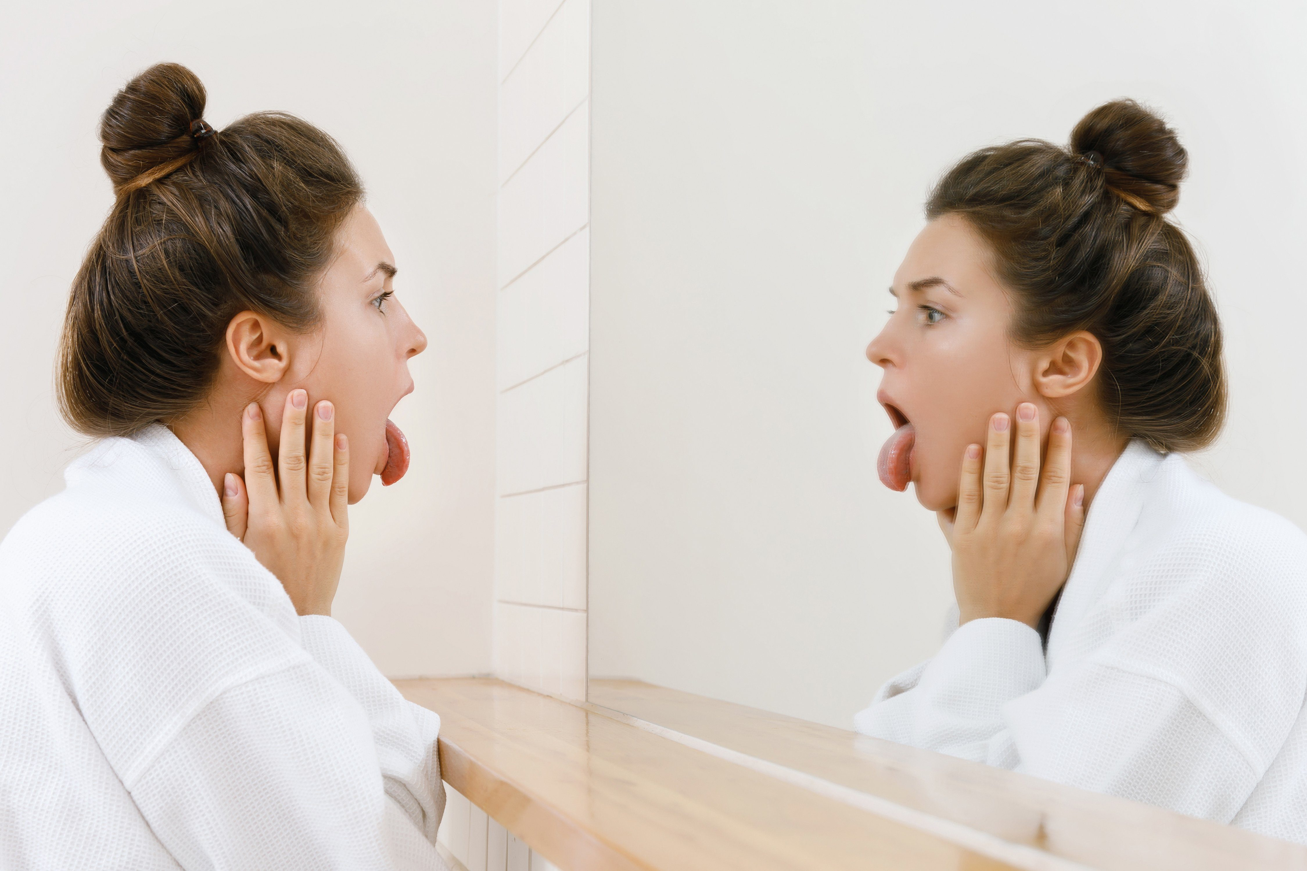 Woman looking on her tongue in the mirror