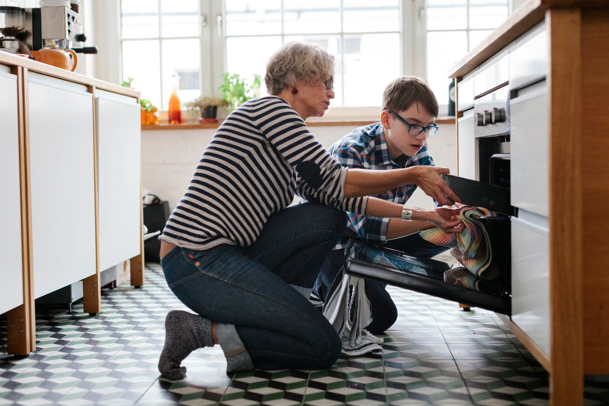 Mature Mother teaching her teenage Son how to bake