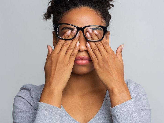 Allergies vs pinkeye - woman rubbing her eyes