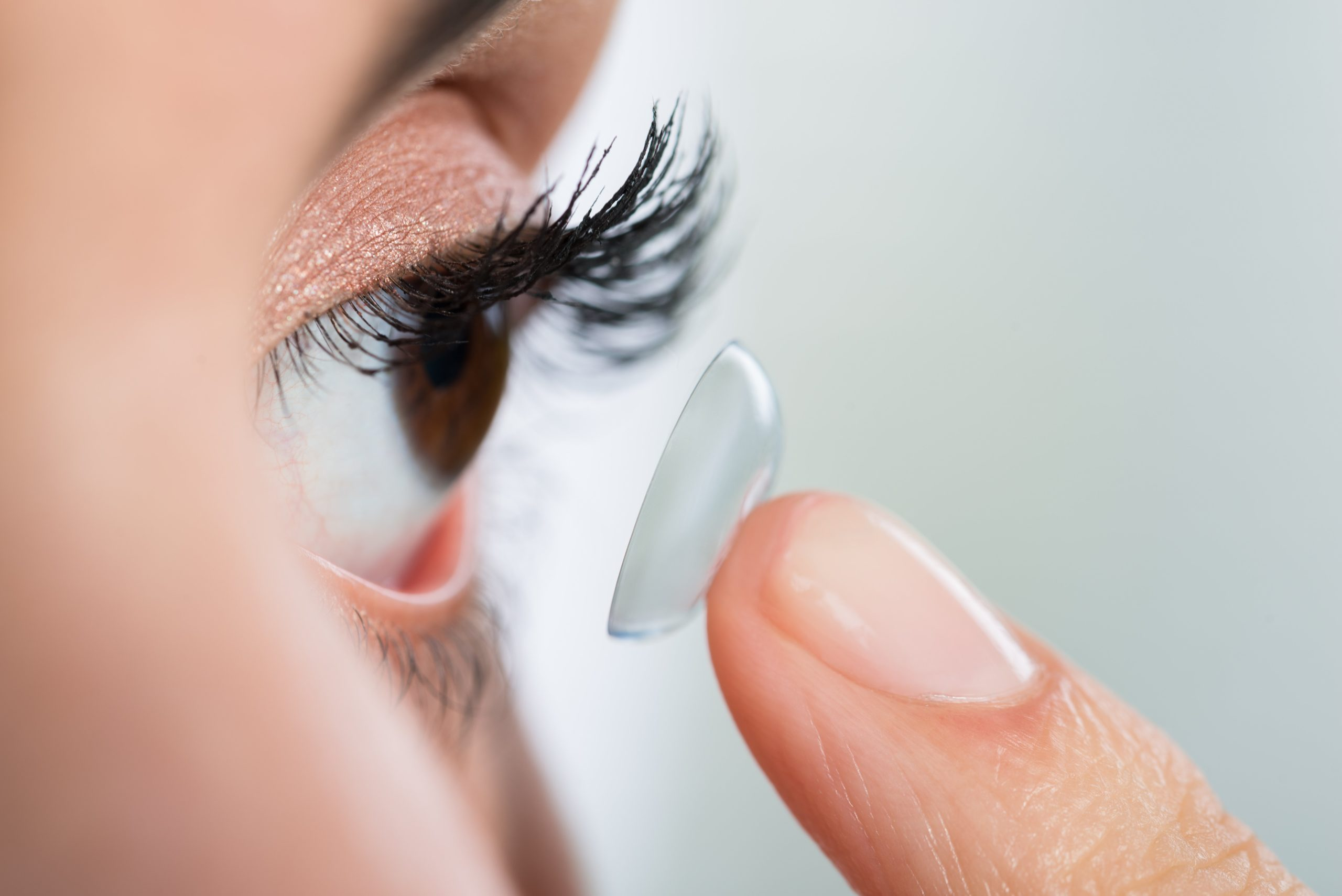 Close-up of young woman wearing contact lens at home