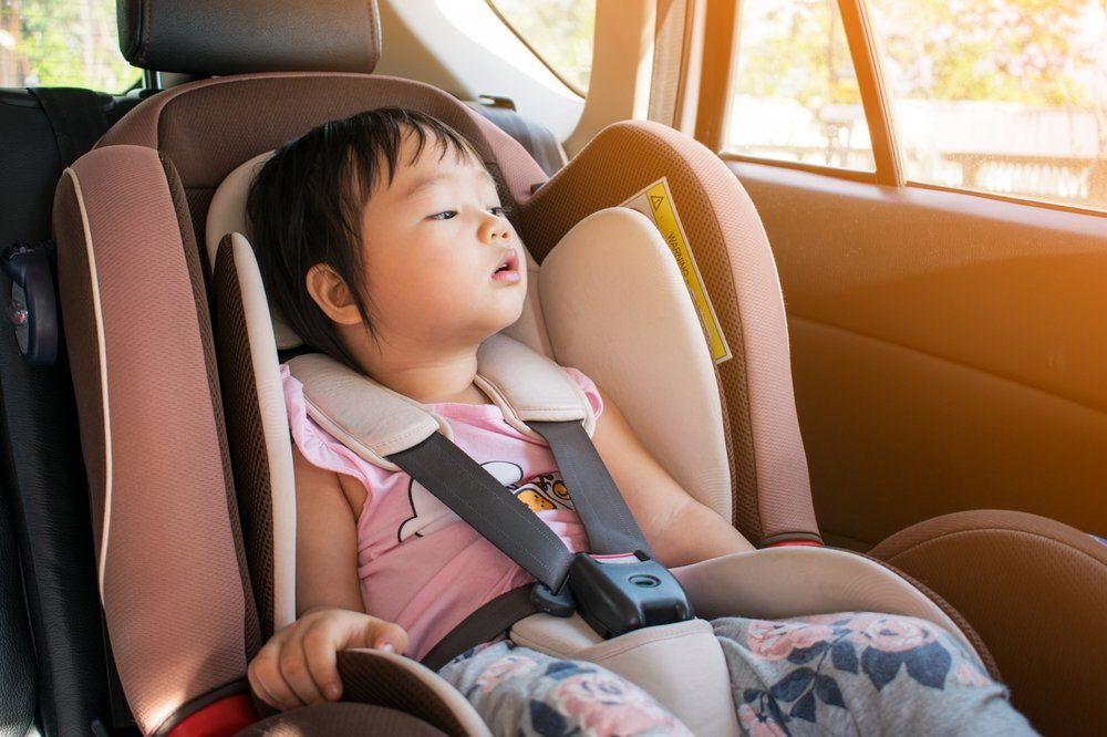Toddler girl sitting in her car seat, looking outside the window.