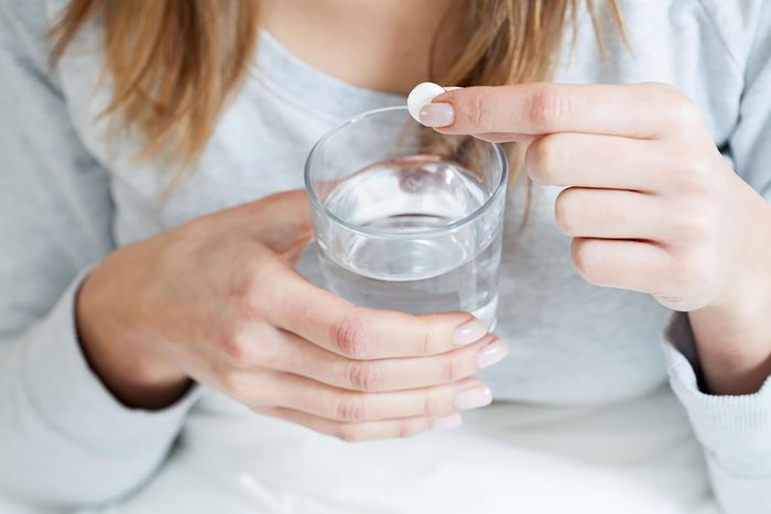 woman holding aspirin and glass of water