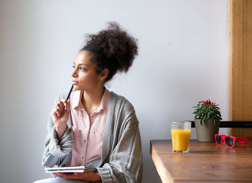 woman sitting and thinking with pen and paper