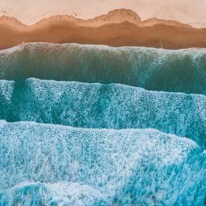 Aerial view of sea waves breaking on shore.