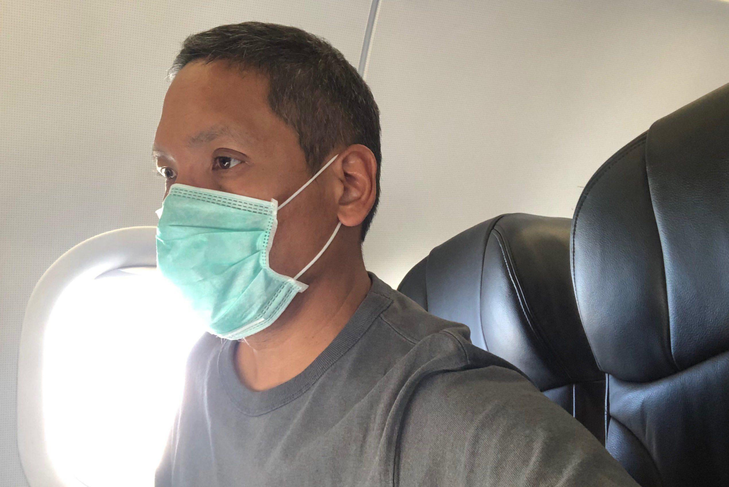 Man Wearing Mask Sitting In Airplane