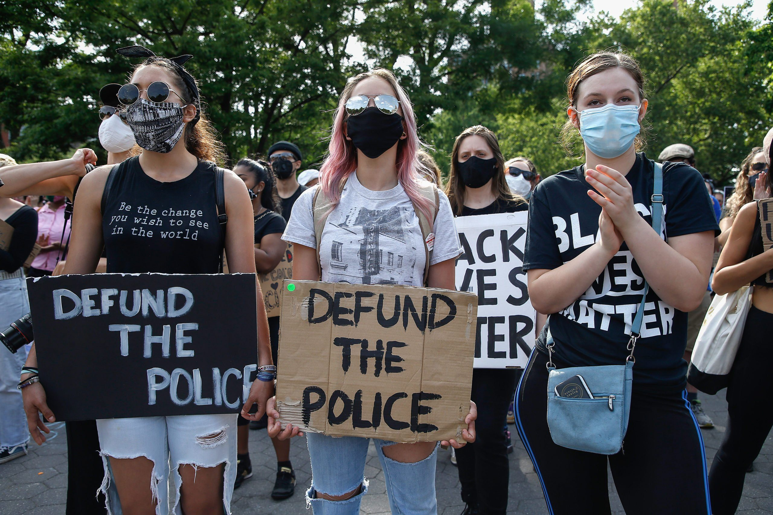 Demonstrators hold placards saying 'Defund The Police'...