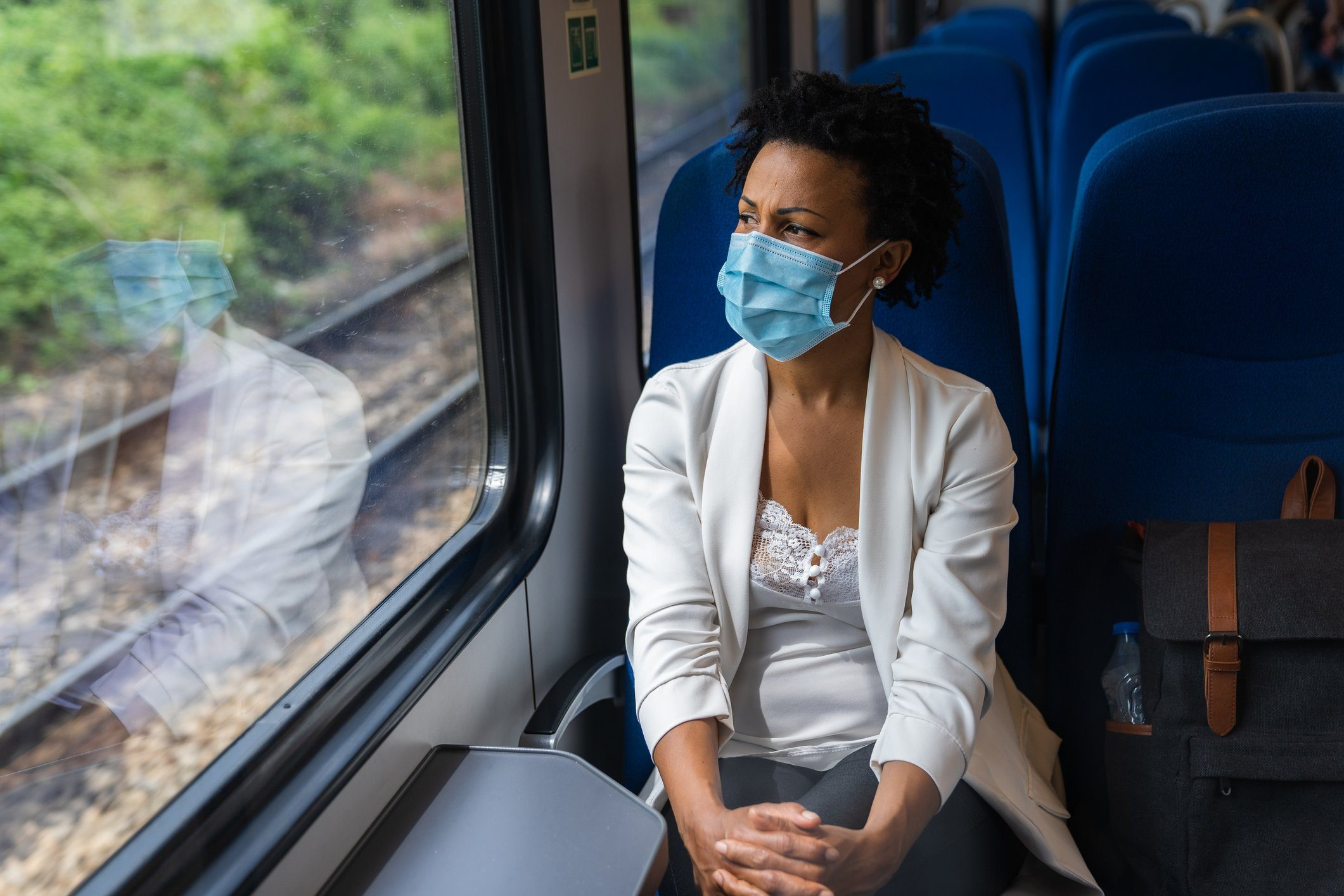 woman sitting on a train looking out the window wearing a face mask