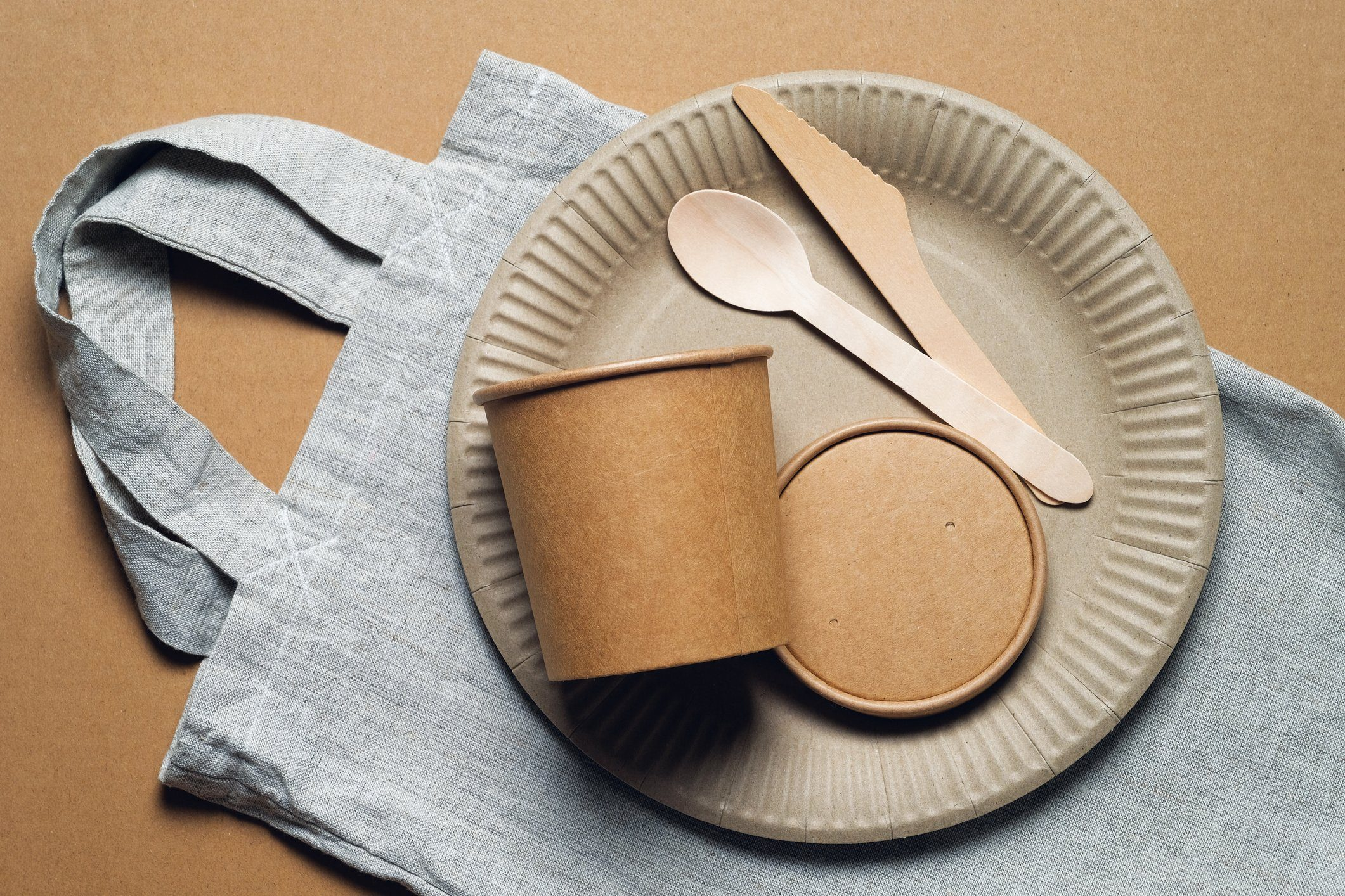 Disposable eco-friendly tableware, reusable bag-string bag on a cardboard background. Secondary use. No plastic. Environmental protection.