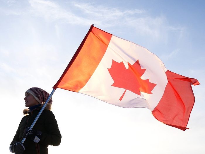 Canada National Anthem - Man on the top with Canadian flag. Winner and motivation concept.