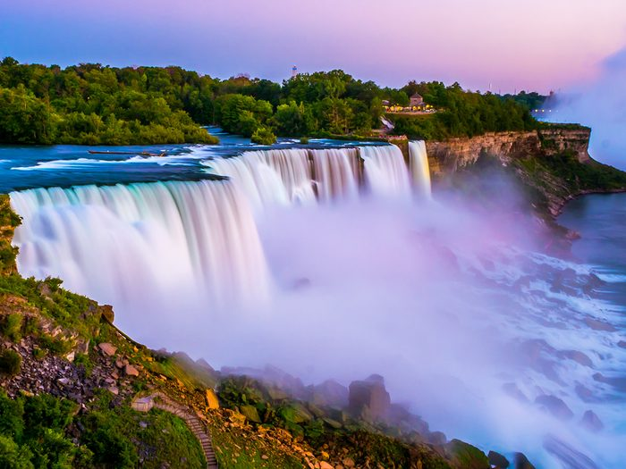 Canada waterfall - Niagara falls in the summer during beautiful evening, night with clear dark sunset blue sky. Niagara fall water hit with many colorful lights that is beautiful in a way. Sky turning dark and cold.